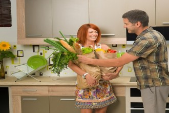 beautiful woman laughing and holding shopping bag with groceries, in kitchen, with a man smiling and trying to help her