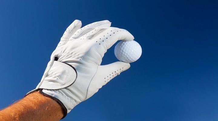 Hand wearing golf glove holding a white golf ball over a deep blue sky.